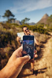 Hiker couple taking pictures with smartphone Royalty Free Stock Photography