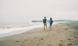 Hiker couple walking on beach Royalty Free Stock Photos