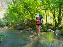Hiker crosses a river Stock Photo