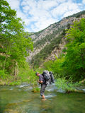 Hiker crosses a river. At the ford Royalty Free Stock Photos