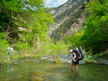Hiker crosses a river Stock Image