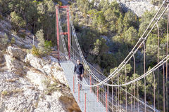 Hiker crossing a bridge in a sunny day Royalty Free Stock Image
