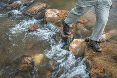 Hiker crossing mountain creek. Legs of a male hiker crossing mountain creek in Colorado foothills Royalty Free Stock Images