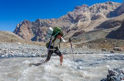 Hiker crossing mountain river Stock Images