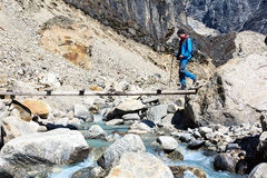 Hiker crossing Mountain River throw wooden Bridge Stock Image