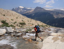 Hiker Crossing Mountain Stream Royalty Free Stock Images