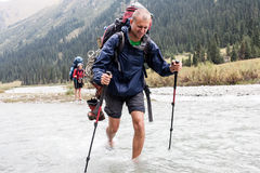 Hiker crossing river at mountains. Stock Photos