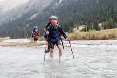 Hiker crossing river at mountains. Stock Photography