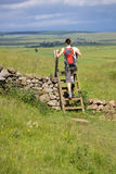 Hiker crossing a Stile Stock Images