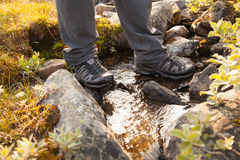 Hiker crossing a stream Stock Photography