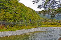 Hiker Crossing a Suspension Bridge over a Wild River Royalty Free Stock Photos