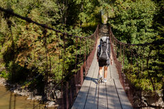 Hiker is crossing suspension bridge Stock Photography