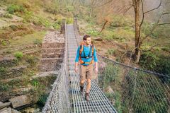 Hiker crossing suspension footbridge Royalty Free Stock Photos