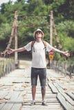 Hiker is crossing wooden bridge in Georgia. Hiker hipster is crossing wooden bridge in Georgia Royalty Free Stock Image
