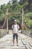 Hiker is crossing wooden bridge in Georgia. Hiker hipster is crossing wooden bridge in Georgia Stock Images