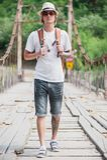 Hiker is crossing wooden bridge in Georgia. Hiker hipster is crossing wooden bridge in Georgia Stock Photo
