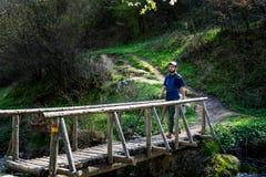Hiker crossing the wooden bridge outdoors stock photo
