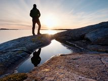 Hiker in dark sportswear with poles and sporty backpack. Coastline trail on rocky shore. Alone tourist enjoy Royalty Free Stock Photos