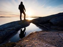 Hiker in dark sportswear with poles and sporty backpack. Coastline trail on rocky shore. Alone tourist enjoy Stock Photos