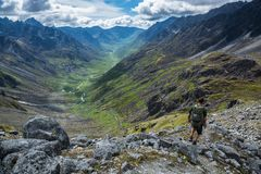 Hiker descending steep rocky trail above glacial valley in Alask Royalty Free Stock Photography