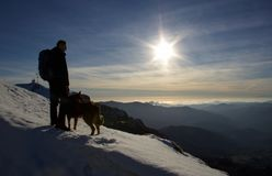 Hiker with a dog looking the horizon from the top of the mountai. N at sunset on ligurian sea Royalty Free Stock Images