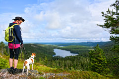 Hiker with dog on mountain. Looking down to walley view Royalty Free Stock Photography