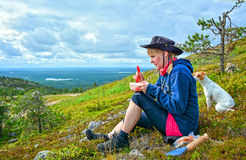 Hiker and dog on mountain. Hiker woman eating and resting on mountain Royalty Free Stock Photos