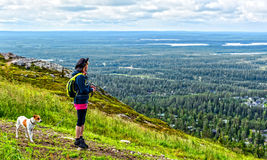 Hiker and dog on mountain. Hiker woman  with dog on mountain looking down to walley view Stock Photos