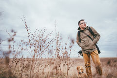 Hiker and dog. Walking in high grass on a cloudy day Royalty Free Stock Photos