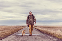 Hiker and dog walking on the road Stock Photos