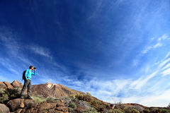 Hiker in dramatic landscape. Hiking under deep blue sky looking in binoculars. Young Caucasian man during hike in Mountain landscape on volcano Teide, Tenerife Stock Images