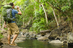 Hiker Drinking Water. A hiker drinks water next to a river Stock Image
