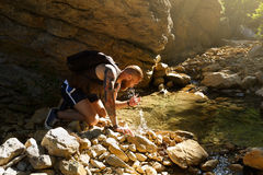 Hiker drinking water from the river. Man enjoys clean fresh unpolluted water in the mountain creek Stock Photos