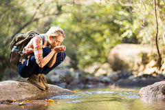 Hiker drinking water. Young hiker drinking stream water in mountain