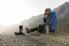 Hiker eats an apple during a break and prepares a hot tea Royalty Free Stock Images