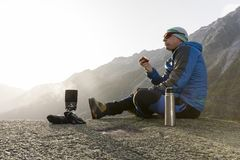 Hiker eats an apple during a break and prepares a hot tea Royalty Free Stock Photos