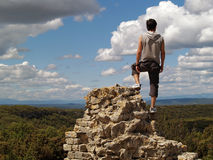 Hiker on the edge of a cliff. Man looking at the scenery from a cliff's edge Stock Images