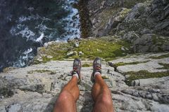 Hiker on the edge of a high cliff stock photography