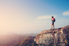 Hiker enjoy the view at sunset mountain peak Stock Photo