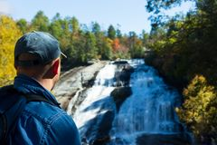 Hiker enjoying the beauty of High Falls in Dupont State Forest in the fall. royalty free stock images