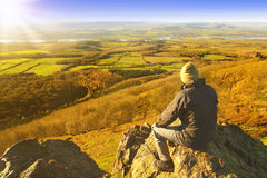 Hiker enjoying rest and landscape. Hiker taking a rest and enjoying beautiful English countryside landscape, relaxation and peace and quiet Royalty Free Stock Photo