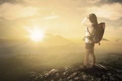 Hiker enjoying sunrise view on mountain Royalty Free Stock Image