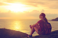 Hiker enjoying sunset listening to music on peak of mountain. Royalty Free Stock Photos