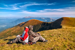 Hiker enjoying valley view from top of a mountain Royalty Free Stock Photos