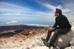 Hiker enjoying view. Hiking - Hiker enjoying view. Male hiker sitting and relaxing at the summit of the volcano Royalty Free Stock Image