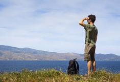 Hiker enjoying the view. Hiker with backpack enjoying the beautiful view of the sea from the Greek island of Hydra, copyspace Royalty Free Stock Photography
