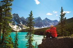 Hiker enjoying the view of Moraine lake in Banff National Park. Alberta, Canada, with snow-covered peaks of canadian Rocky Mountains in the background Royalty Free Stock Image