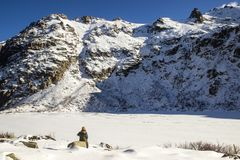 A hiker in front of the Melu lake, frozen, Corsica. stock photography