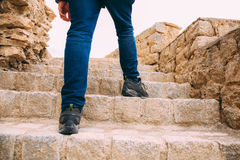Hiker or Explorer going up on the stairs to archaeological site - Expedition and world explore Stock Image