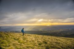 Hiker in field at sunset Royalty Free Stock Image
